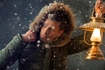 Brutal man walking under snowstorm at night lighting his way wit