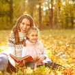 Mother and daughter having fun in the autumn park among the fall