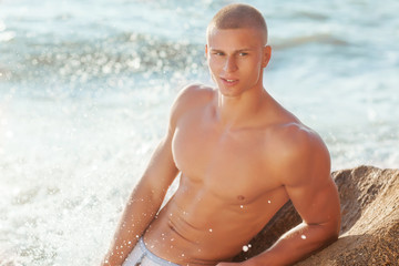 Portrait of a handsome young muscular man in swimtrunks