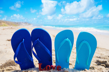 "Flip flops with sign ""Love"" on the beach"