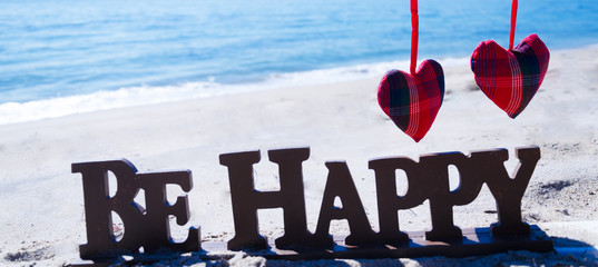 "Sign ""Be happy"" with heart on the beach"