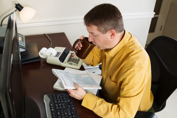 Mature man working on his income taxes while in the office