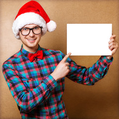 Hipster Santa Claus pointing in white blank sign with smile
