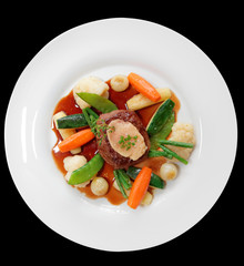 Tenderloin steak with vegetables and bone marrow isolated on bla