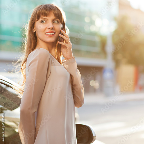 Sophisticated businesswoman in dress talking on the phone.