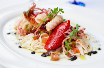 Pasta with seafood on oval porcelain plate