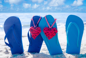 Flip flops with hearts on the beach