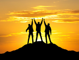 Silhouette of a team on the mountain top.