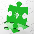 Business concept: Light Bulb on puzzle background