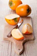 ripe persimmons and knife
