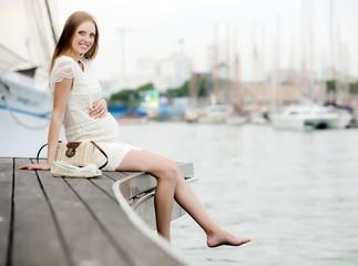 Happy pregnant  woman in sea port