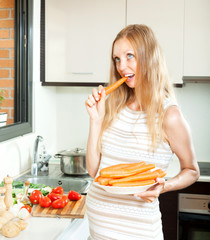Casual positive pregnant girl eating carrots  at kitchen