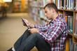 Thoughtful young student sitting on library floor using tablet