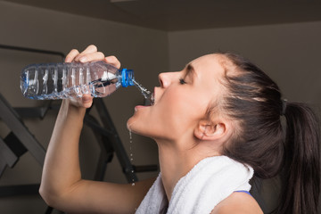Close-up of a young woman drinking water in gym