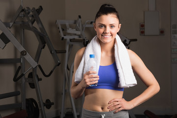 Smiling woman with water bottle standing in the gym