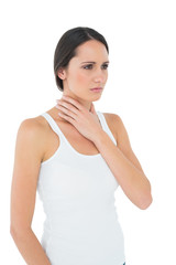 Serious casual young woman suffering from neck ache