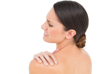 Close-up of a topless young woman with shoulder pain