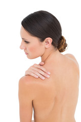 Close-up of a topless woman with shoulder pain