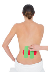 Topless fit woman with red and green strips on back