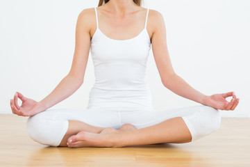 Toned woman in lotus pose at fitness studio