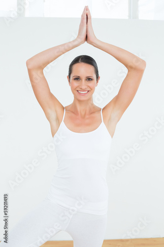 Sporty woman with joined hands over head at a fitness studio