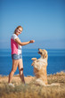 Beautiful woman with her dog playing on the sea shore. Outdoor p