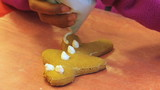 Putting Icing On Christmas Gingerbread Man Cookie