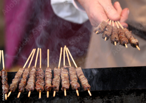 Cook's hand turns the meat skewers of roasted beef