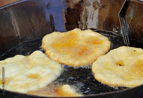 tasty Fried Apple fritters in the cauldron of boiling oil on sal