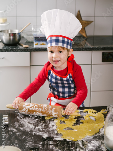 Happy young boy making cookies