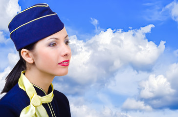 Beautiful young stewardess in profile on the sky background
