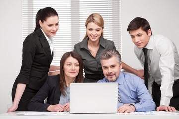Large group of people looking together at laptop.