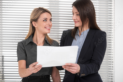 business woman explaining and teaching young  female employee.