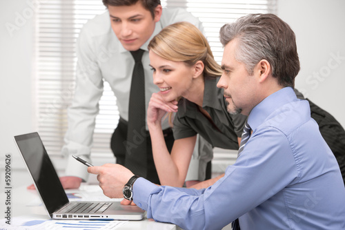 Senior  business man showing something on laptop.
