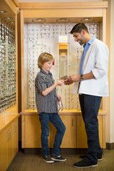 Optometrist And Boy Holding Spectacles In Store