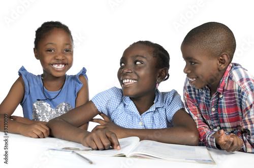 Leinwanddruck Bild Drei afrikanische Kinder beim Lernen