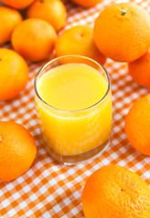 Glass of orange juice with some tangerines
