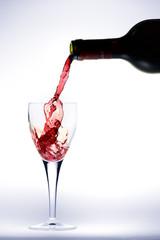 Bottiglia che versa vino rosso nel bicchiere