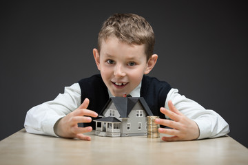Little boy taking away house model and pile of coins