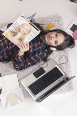 Casual blogger woman reading a magazine in her fashion office.