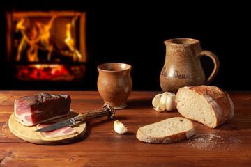 Vesperbrot mit Schinkenspeck und Wein vor einem Feuer