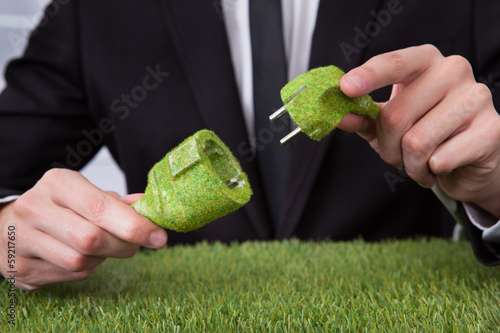 Man Holding Grass Covered Cable