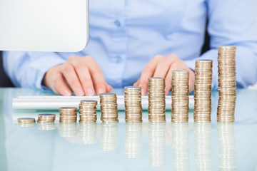 Coins Stacked On Desk In Front Of Businesswoman