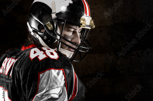 Portrait of thoughtful american football player on dark backgrou