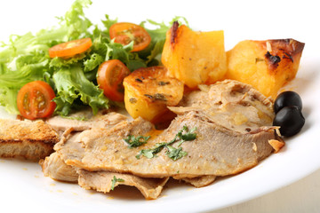 roast pork beef dish with salad and potatoes