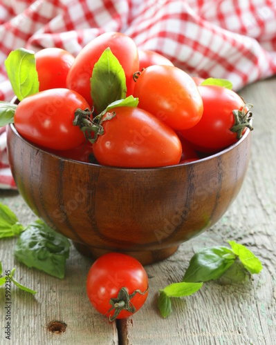 cherry tomatoes with basil leaves in a wooden bowl