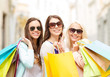 three smiling girls with shopping bags in city