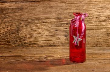 Rote Glasflasche vor einem Holzhintergrund