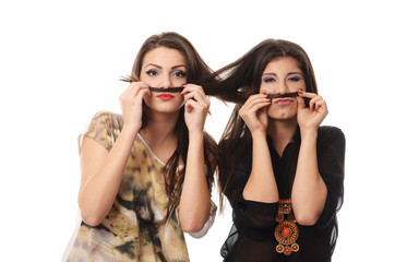 Girls having fun and making mustaches out of each others hair