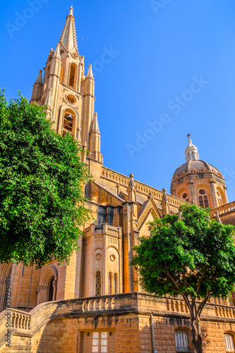 The Ghajnsielem Parish Church behind the trees in Gozo, Malta
